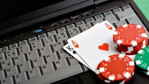 a laptop keyboard with poker chips and cards next to it