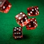 red dices being thrown on a green casino table