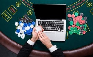 a laptop on a casino table with poker chips next to it