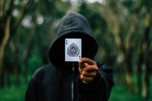 a mysterious man with a black hoodie holding an ace