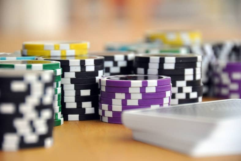 black green purple and yellow poker chips stacked on a table
