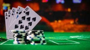playing cards with black and white poker chips laying on a green casino table
