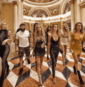dan bilzerian in a hotel hall being surronded by girls in short dresses walking