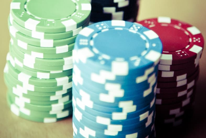green, blue, red and black poker chips stacked on a table