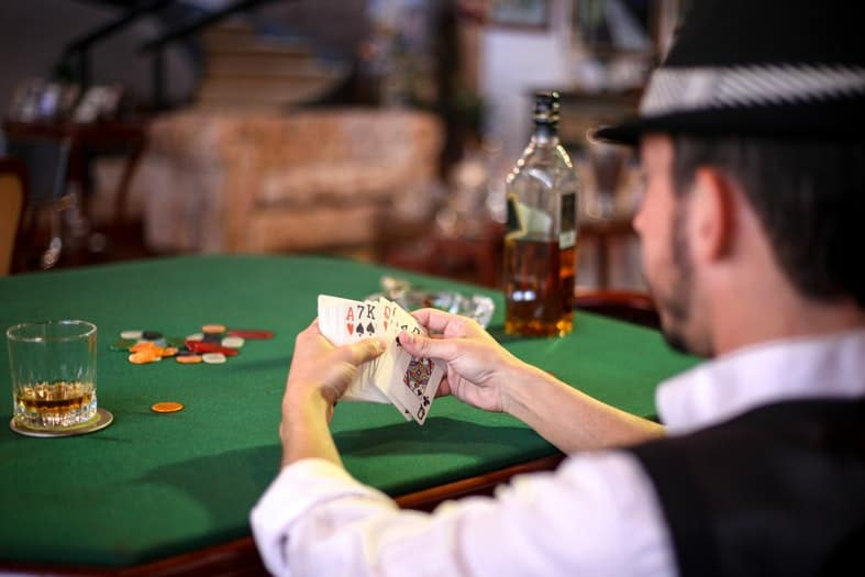 a man with a hat holding poker cars in his hansd while drinking whiskey
