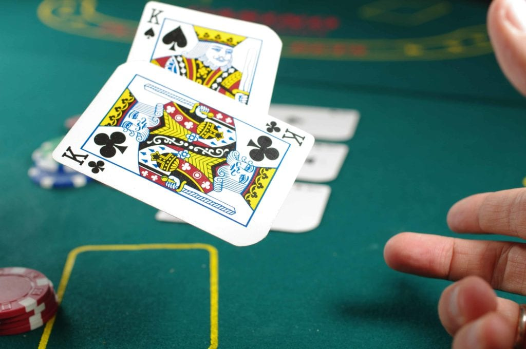 a man throwing two king cards on a green poker table