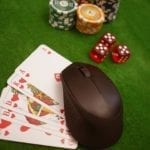 a green poker table with cards, cubes and poker chips and a computer mouse on the cards