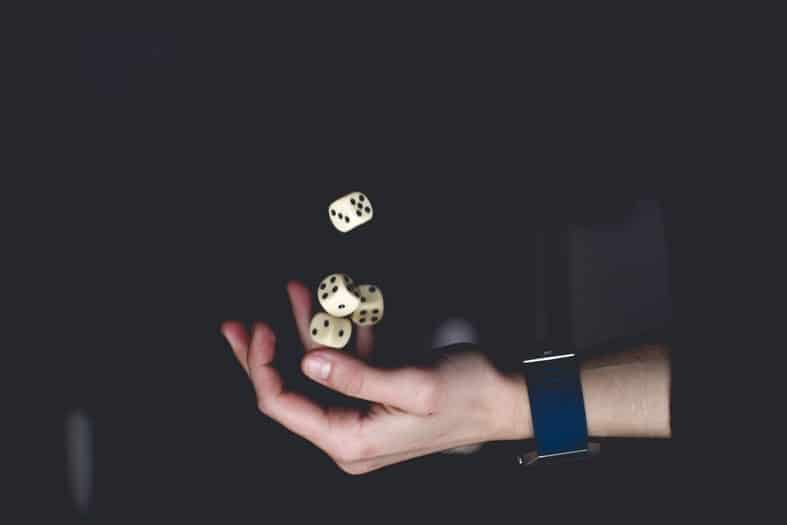 a hand with a black watch throwing 4 cubes in the air
