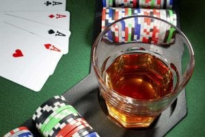 whiskey, poker cards and chips on a green poker table