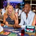 a couple of people sitting on a casino table laughing
