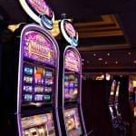 two slot machines standing next to each other in a casino room